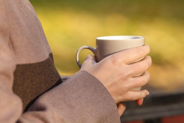 Sluit omhoog van vrouw het drinken van een kop tegen het patroon van de herfstbladeren