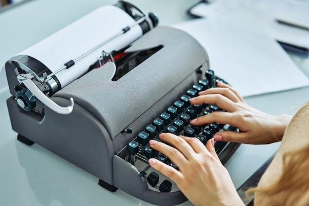 Sluit omhoog van vrouw het typen met oude schrijfmachine