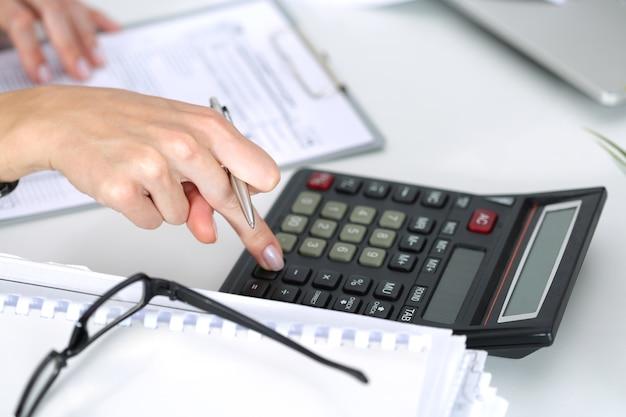 Sluit omhoog van vrouwelijke accountant of bankier die berekeningen maken. besparingen, financiën en economieconcept
