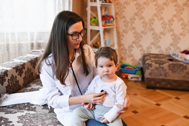 Sluit omhoog van vrouwelijke arts met stethoscoop thuis luisterend aan de hartslag of de adem van de patiënt