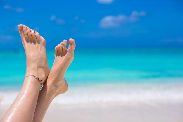 Sluit omhoog van vrouwelijke benen op wit zandig strand
