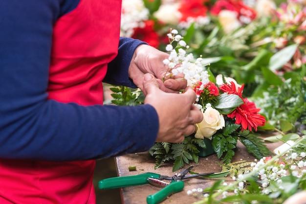 Sluit omhoog van vrouwelijke bloemist die tot mooi boeket leiden bij bloemwinkel.