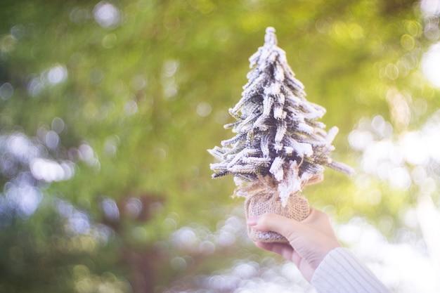 Sluit omhoog van vrouwelijke handen houdend kerstmisdecoratie, een kleine kerstmisboom.