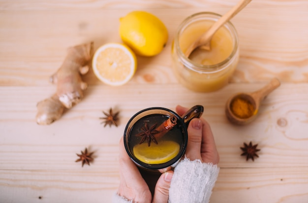 Sluit omhoog van vrouwelijke handen houdend kop van warm water met citroen