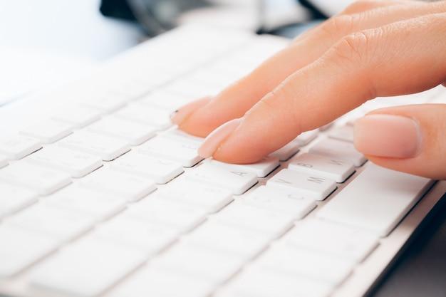 Sluit omhoog van vrouwelijke handen van vrouwenbeambte het typen op het toetsenbord