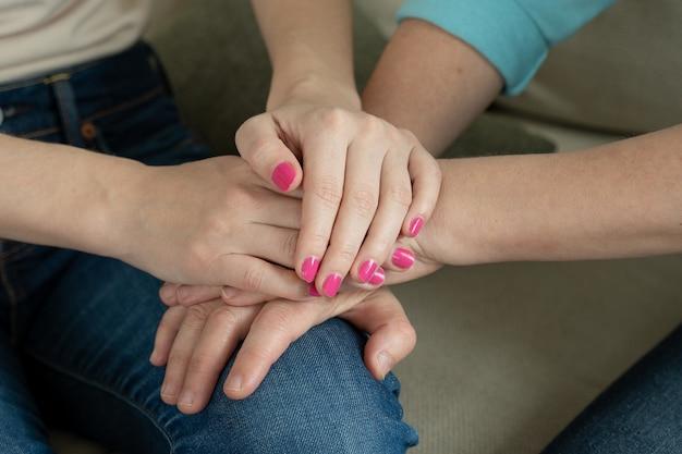 Sluit omhoog van vrouwelijke jonge handen die de handen van een oudere vrouw houden