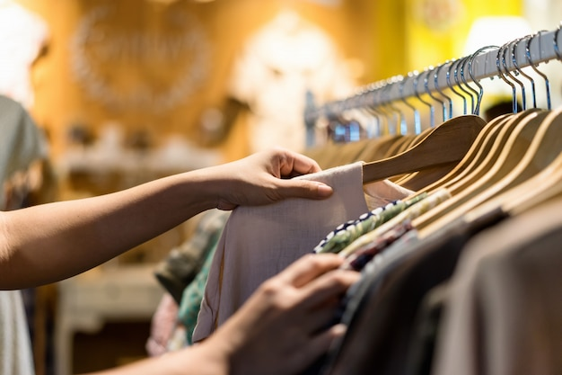 Sluit omhoog van vrouwenhand die de kleren van de zuinigheidsjong en kortingst-shirt in opslag kiezen