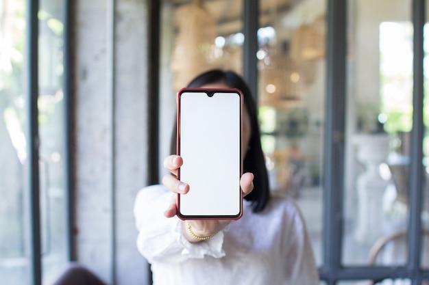 Sluit omhoog van vrouwenhand die het lege telefoonscherm tonen. concept van technologiecommunicatie.