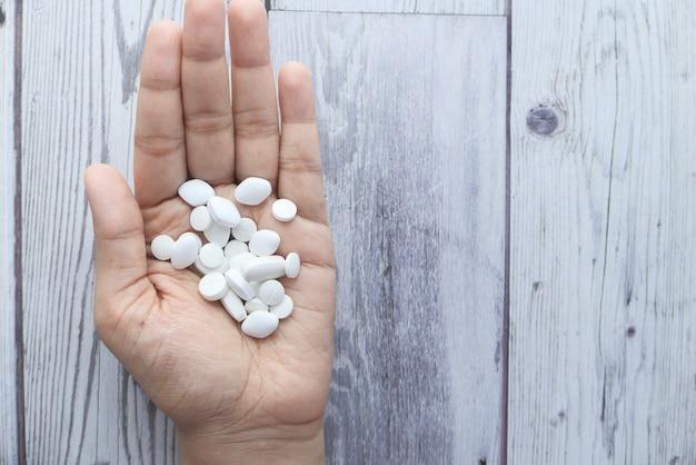 Sluit omhoog van vrouwenhand die pillen nemen