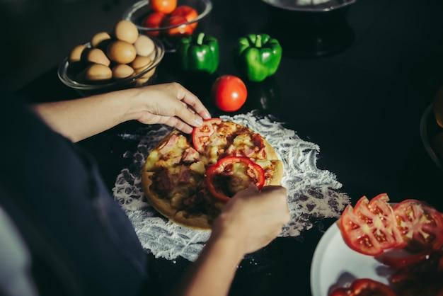 Sluit omhoog van vrouwenhand gezet bovenste laagje op eigengemaakte pizza.