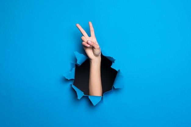 Sluit omhoog van vrouwenhand met vredesgebaar door blauw gat in document muur.