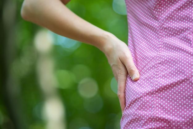 Sluit omhoog van vrouwenhand op haar taille.