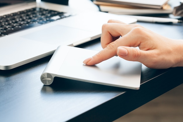 Sluit omhoog van vrouwenhand wat betreft op laptop het stootkussen van de computermuis