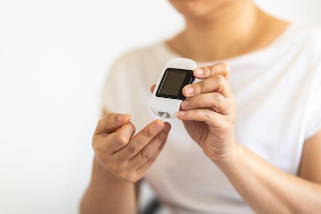 Sluit omhoog van vrouwenhanden die glucosemeter op vinger gebruiken om bloedsuikerspiegel te controleren.
