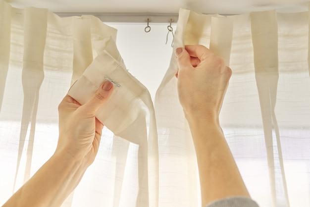 Sluit omhoog van vrouwenhanden die gordijn met metaalhaken op plafondrichel hangen