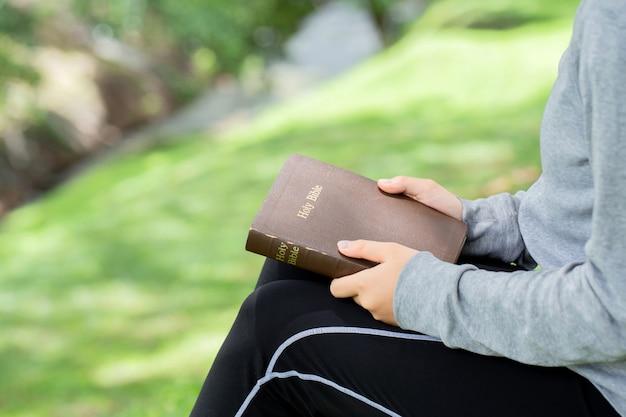 Sluit omhoog van vrouwenhanden die heilige bijbel op groene achtergrond met bokehlicht houden, exemplaarruimte
