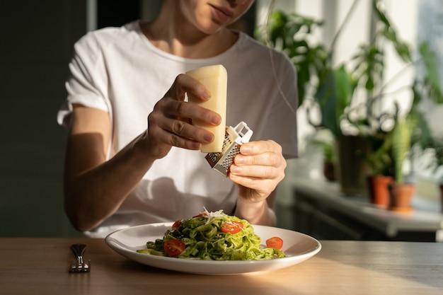 Sluit omhoog van vrouwenhanden die parmezaanse kaas in deegwaren met sauspesto, verse kersentomaten raspen.
