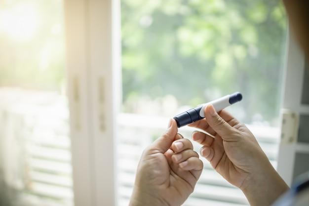Sluit omhoog van vrouwenhanden gebruikend lancet op vinger om de bloedsuikerspiegel van diabetes te controleren.