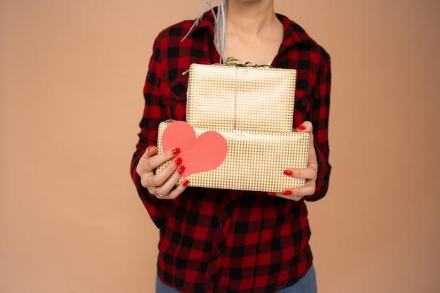 Sluit omhoog van vrouwenhanden op heilige valentijnsdag met rood hartvalentijnskaart en giftdozen die op beige achtergrond worden geïsoleerd