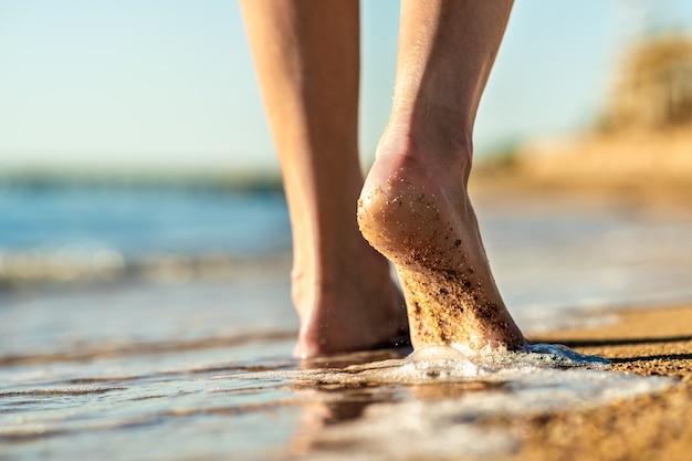 Sluit omhoog van vrouwenvoeten blootvoets lopend op zandstrand in zeewater. vakantie, reizen en vrijheid concept. mensen ontspannen in de zomer.