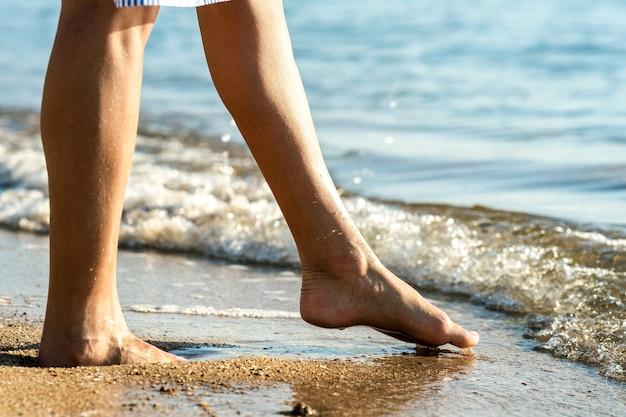 Sluit omhoog van vrouwenvoeten die blootsvoets op zand lopen en voetafdrukken op gouden strand verlaten