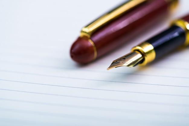 Sluit omhoog van vulpen of inktpen met notitieboekjedocument