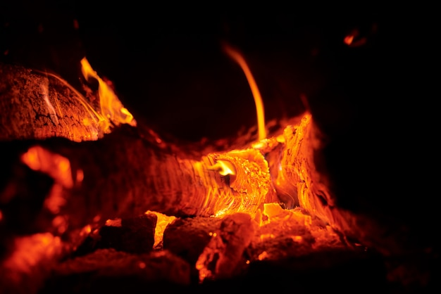 Sluit omhoog van vuur met vonken bij nacht. warmte van brandende houtblokken en kolen in het donker