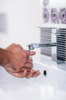 Sluit omhoog van washanden met zeep onder lopend water bij badkamersgootsteen