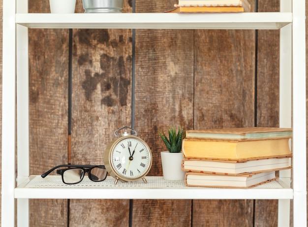 Sluit omhoog van wit boekenrek tegen grunge houten muur