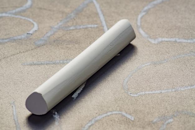 Sluit omhoog van wit krijt op bord met geschreven woorden.
