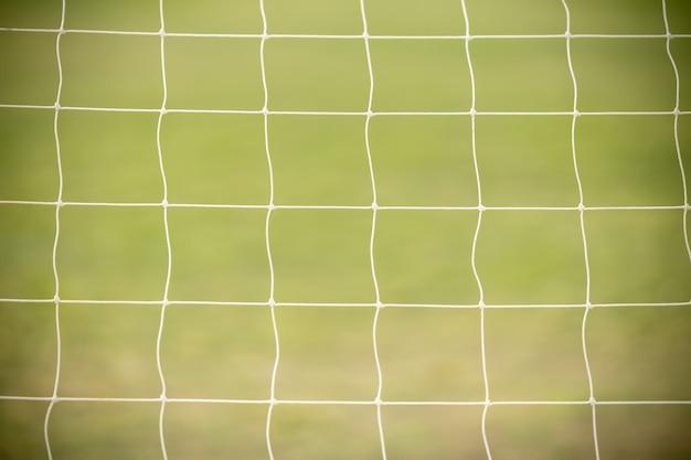 Sluit omhoog van wit voetbal / voetbaldoel netto met groen gras als achtergrond gebruikend als sportbehang of achtergrond.