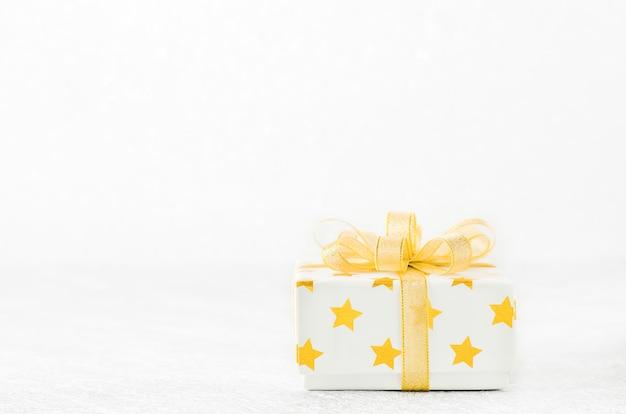 Sluit omhoog van witte giftdoos met gouden sterpatroon en gouden lintboog