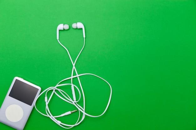 Sluit omhoog van witte oortelefoons met muziekspeler op groenboekachtergrond.