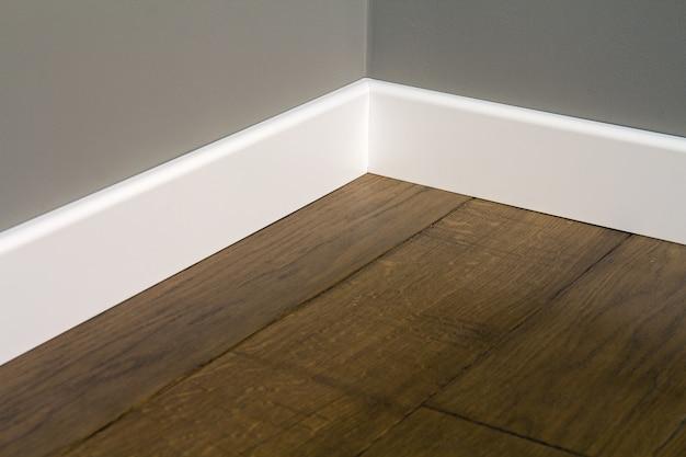 Sluit omhoog van witte plastic plinten op donker houten eiken vloerparket.