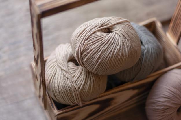 Sluit omhoog van wol het breien op houten achtergrond