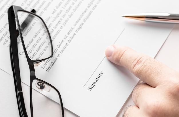 Sluit omhoog van zakenman die naar de handtekeningsregel in contract richt