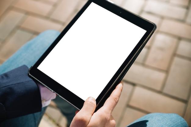 Sluit omhoog van zakenman die tablet in openlucht gebruikt