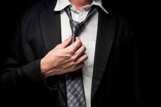 Sluit omhoog van zakenman die zijn band op zwarte achtergrond opstijgt