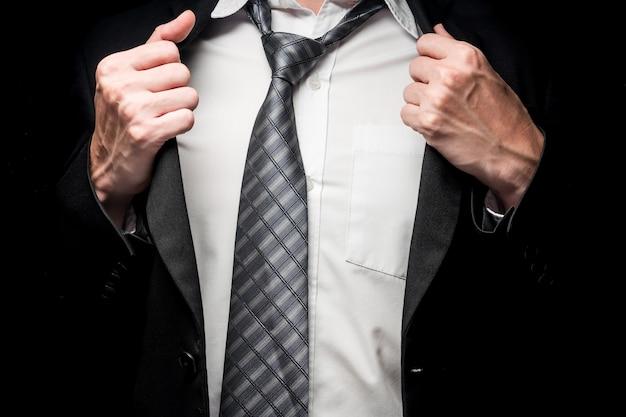 Sluit omhoog van zakenman die zijn kostuum op zwarte achtergrond opstijgt