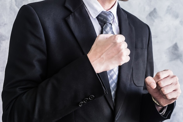 Sluit omhoog van zakenman in zwart kostuum het vechten op grungeachtergrond.