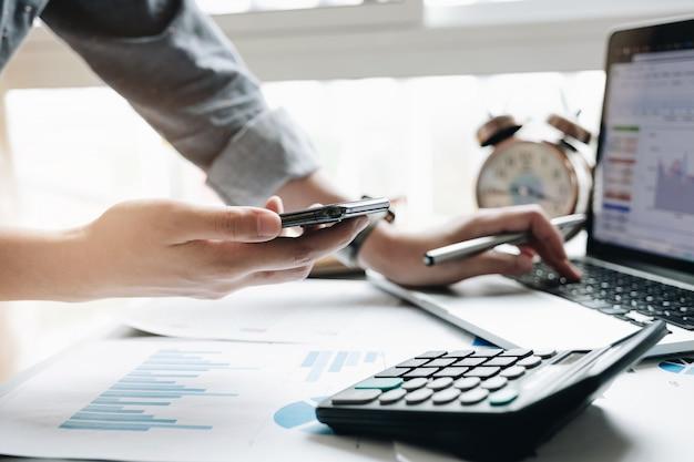 Sluit omhoog van zakenman of accountant de pen die van de handholding aan calculator werken om bedrijfsgegevens te berekenen
