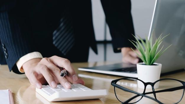 Sluit omhoog van zakenman of accountant de pen die van de handholding aan calculator werkt om bedrijfsgegevens te berekenen