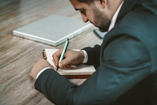 Sluit omhoog van zakenman writing in notebook