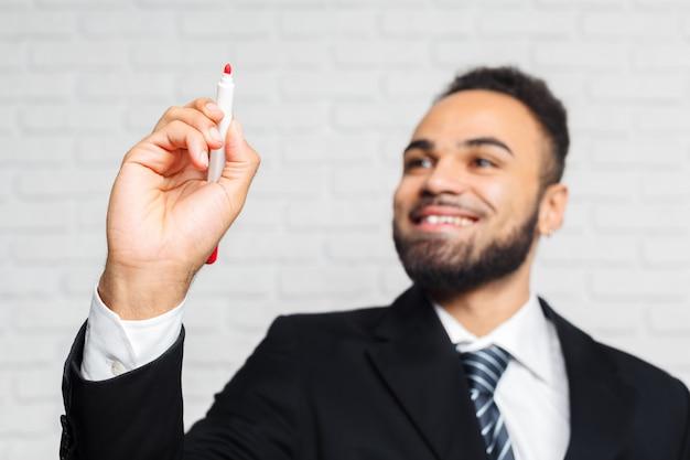 Sluit omhoog van zakenmanhand met pen klaar om iets in het bureau te schrijven
