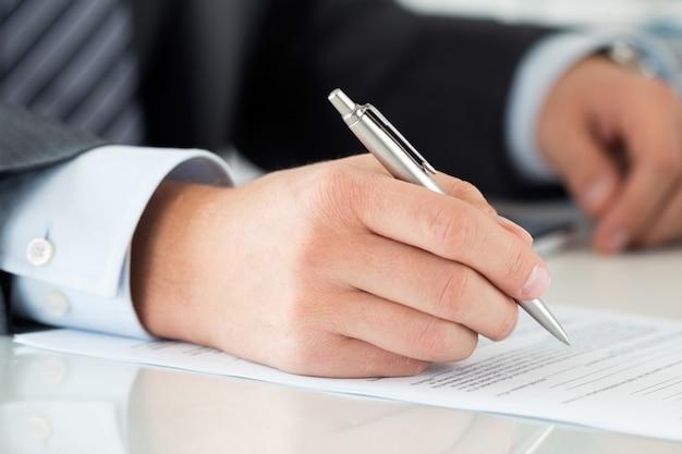 Sluit omhoog van zakenmanhanden die documenten ondertekenen. man schrijven iets zittend op zijn kantoor. partnerschapsovereenkomst van contactondertekening, eindsaldo of het maken van financieel rapportconcept