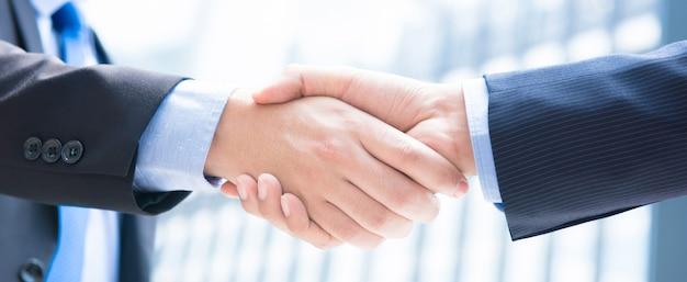 Sluit omhoog van zakenmanhanden die handdruk maken