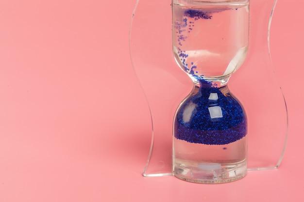 Sluit omhoog van zandloper tegen roze achtergrond