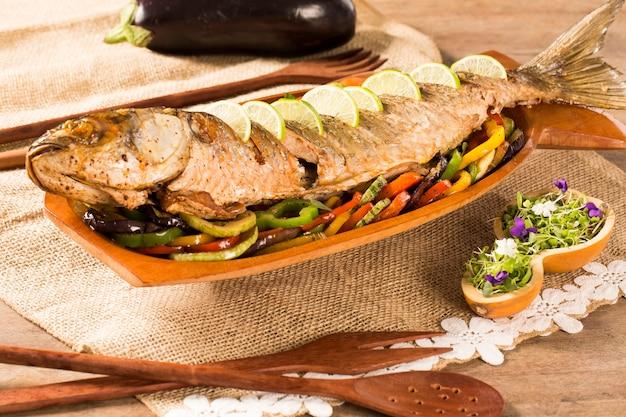 Sluit omhoog van zeebrasemvissen met groente.