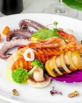 Sluit omhoog van zeevruchtenplaat met de geroosterde garnalen en de mosselen van de zalmoctopus