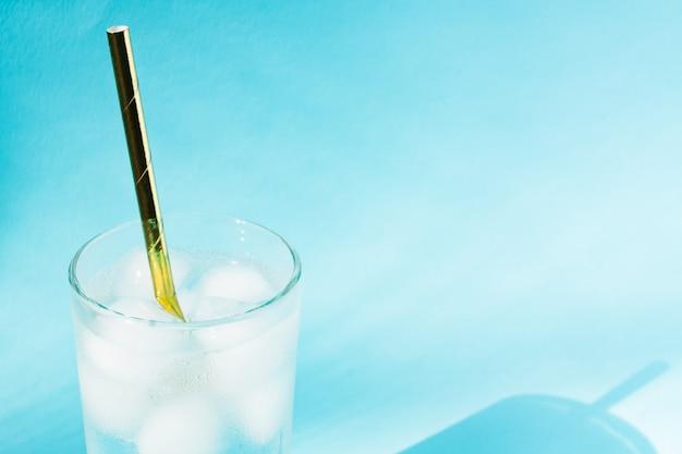 Sluit omhoog van zuiver water met ijs en document stro in transparante glas en zonglans.